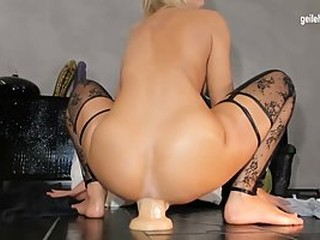 German blonde is demonstrating her masturbation routine in front of the camera, with a huge sex toy