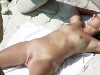 He plays with her pussy and fucks it on the beach