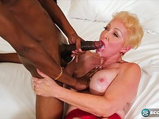Seka Black is having an interracial sex adventure with a black man, in her huge bed